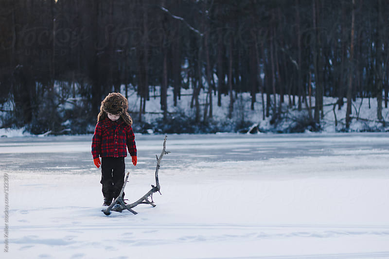 Boy on Frozen Lake Looking Down at Branch by Kevin Keller for Stocksy United