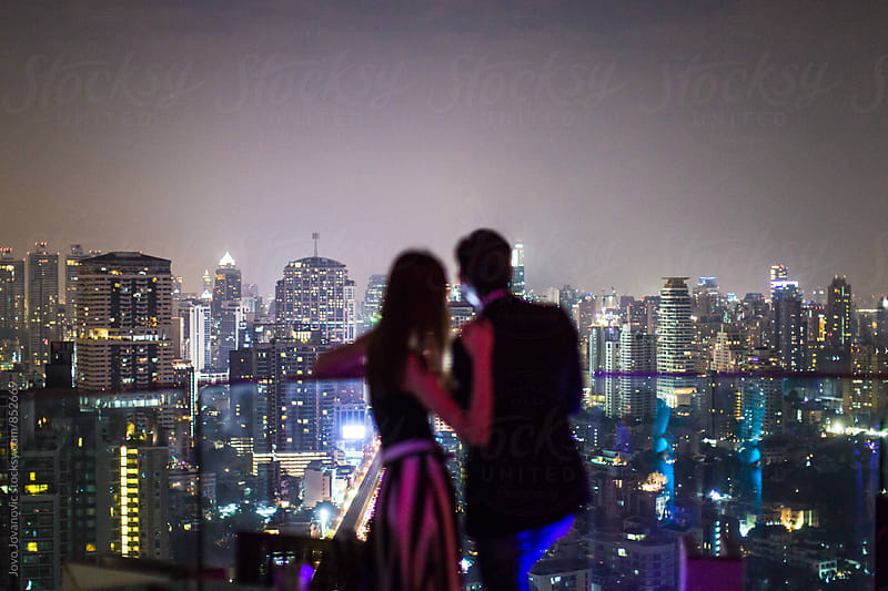 Silhouettes of a stylish young couple looking at the city lights from a modern rooftop bar lounge  by Jovo Jovanovic for Stocksy United
