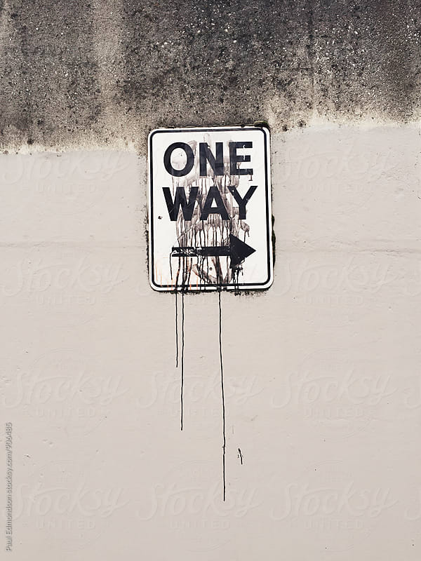 One Way directional sign on wall, paint dripping below by Paul Edmondson for Stocksy United