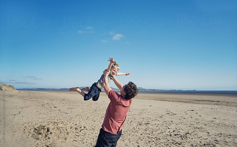 Father and son playing on the beach by sally anscombe for Stocksy United