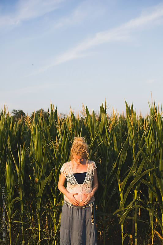Pregnant woman looking at her belly in a field of corn by michela ravasio for Stocksy United