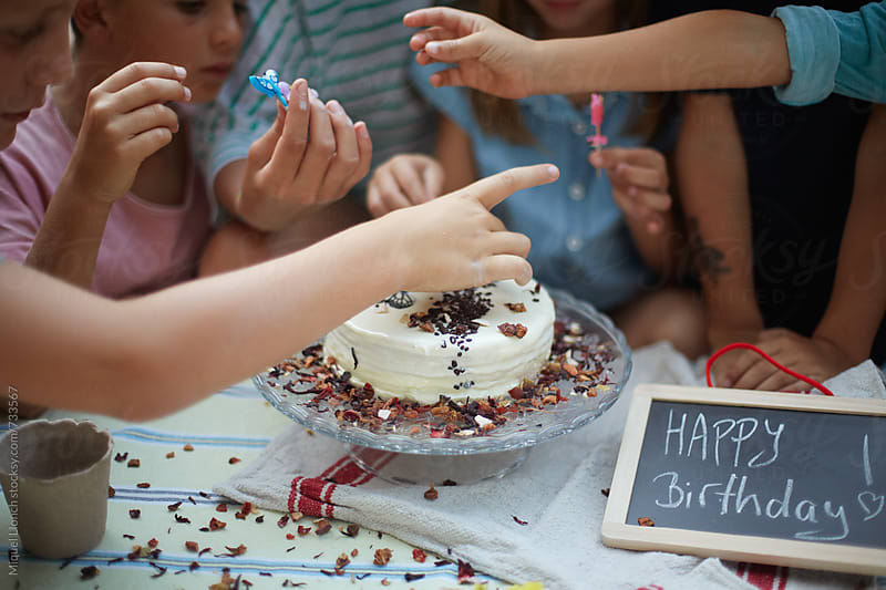 Close up of a birthday cake and children taking the candles of by Miquel Llonch for Stocksy United