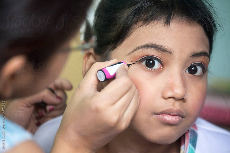 Mother doing make up for her daughter  by PARTHA PAL for Stocksy United