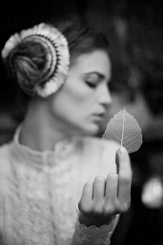 Beauty sideview of young woman with leaf in hand by Ani Dimi for Stocksy United