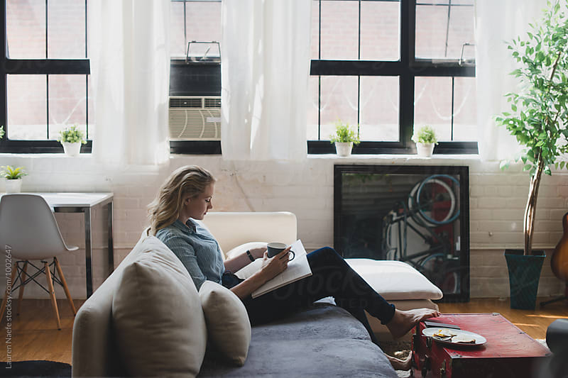 Young woman reading magazine at home by Lauren Naefe for Stocksy United
