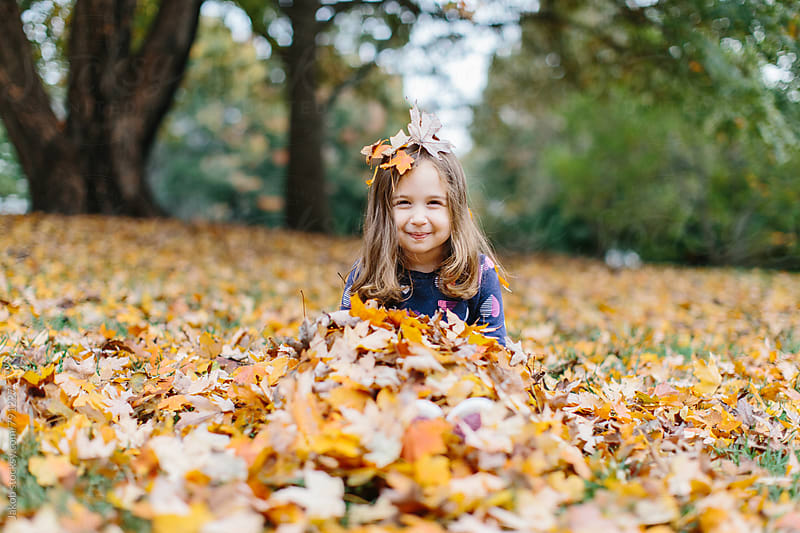 Cute young girl covered in leaves by Jakob for Stocksy United