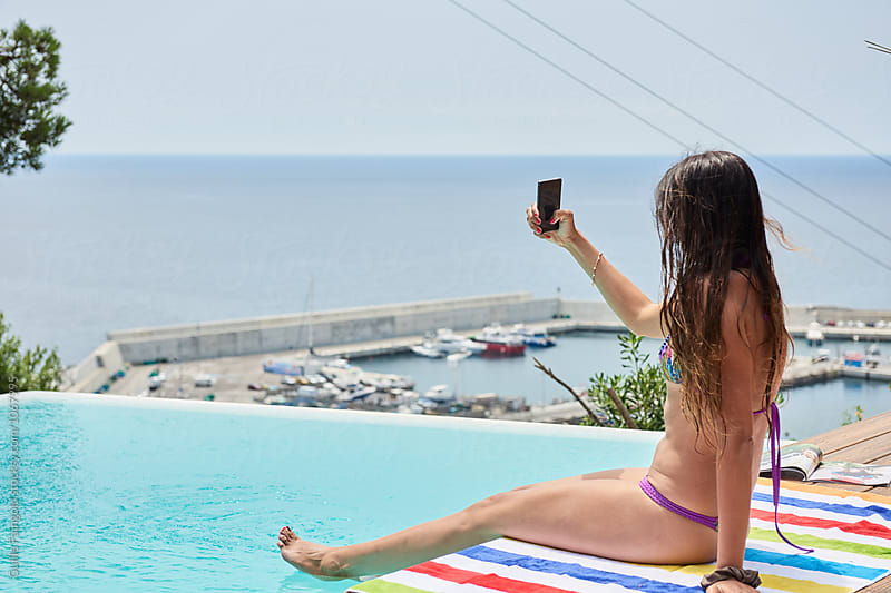Brunette taking selfie at pool by Guille Faingold for Stocksy United