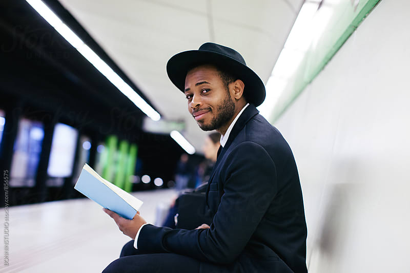 Side view of a businessman reading a book on subway station. by BONNINSTUDIO for Stocksy United