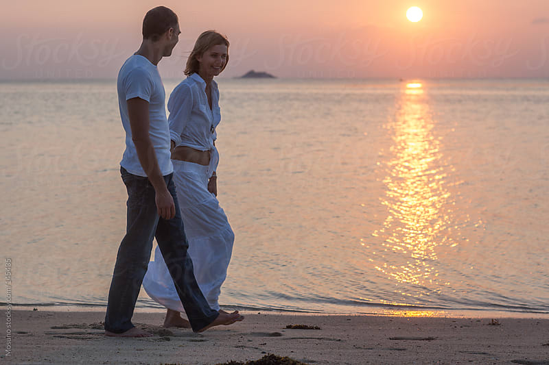 Couple Taking a Walk Down the Beach at Sunset by Mosuno for Stocksy United
