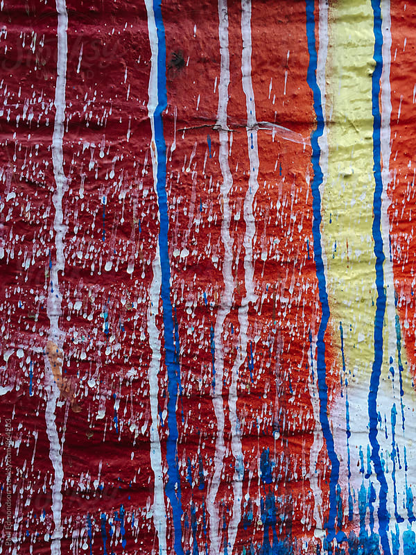 Colorful dripping paint and graffiti on building wall, close up by Paul Edmondson for Stocksy United
