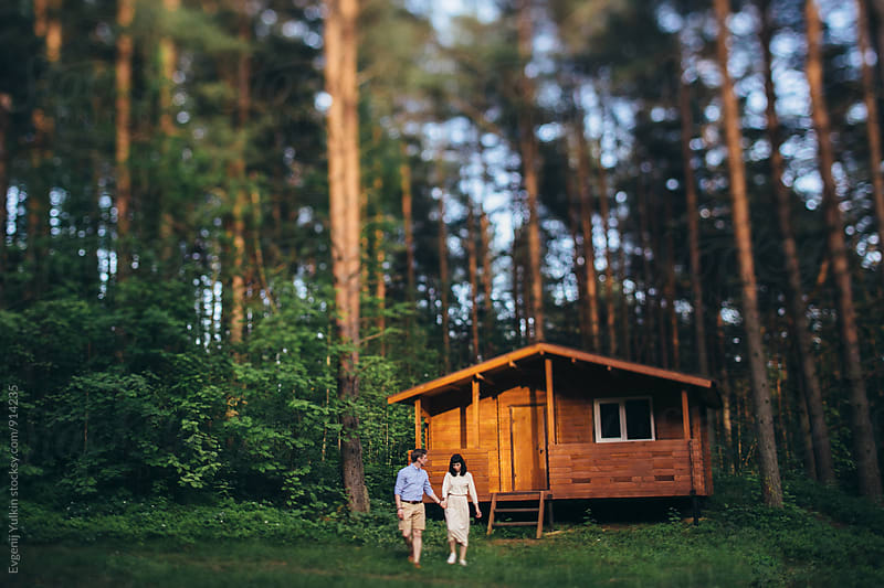 Young couple and their house in the forest by Evgenij Yulkin for Stocksy United