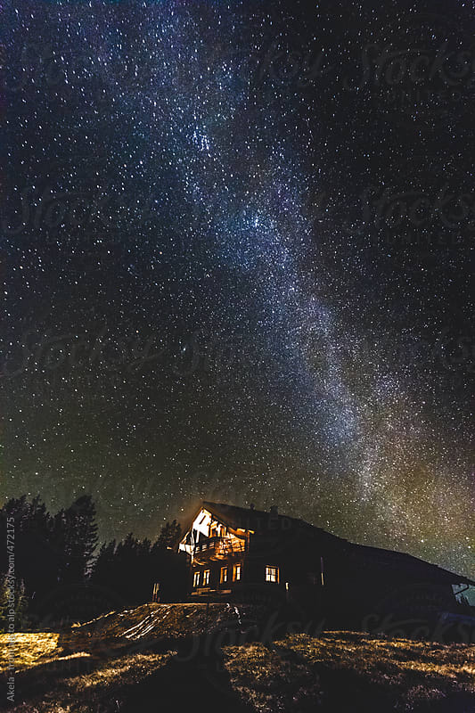 alpine cabin in the mountains at night with the milky way above by Leander Nardin for Stocksy United