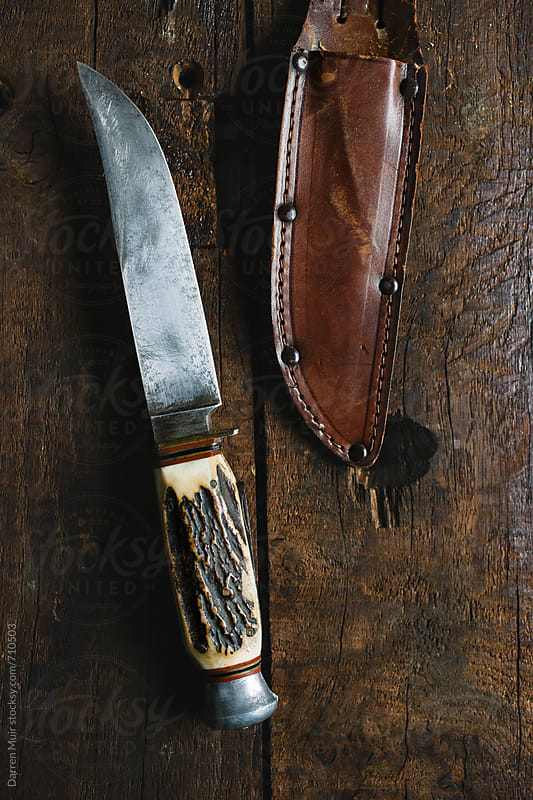 Old hunting knife with leather sheath on wood background. by Darren Muir for Stocksy United