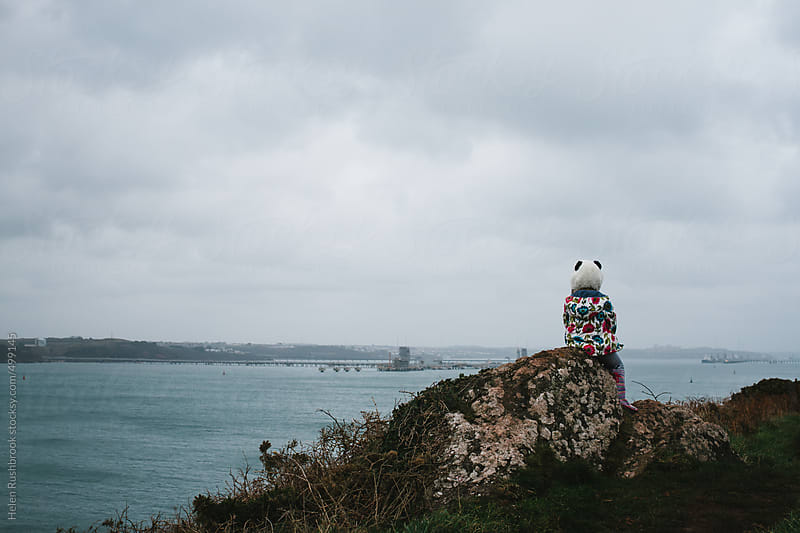 A little girl in a panda hat sitting on a rock looking at the sea. by Helen Rushbrook for Stocksy United
