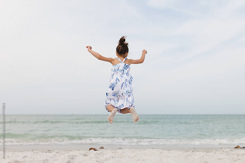 Young girl jumping high in the sand by Amanda Worrall for Stocksy United