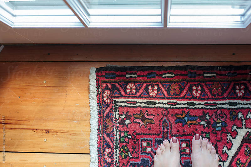 Looking down on a woman's feet standing on an oriental carpet. by Holly Clark for Stocksy United