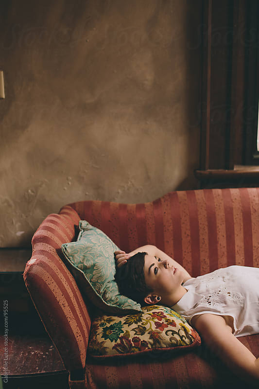 Profile of beautiful girl lying on vintage couch by Gabrielle Lutze for Stocksy United