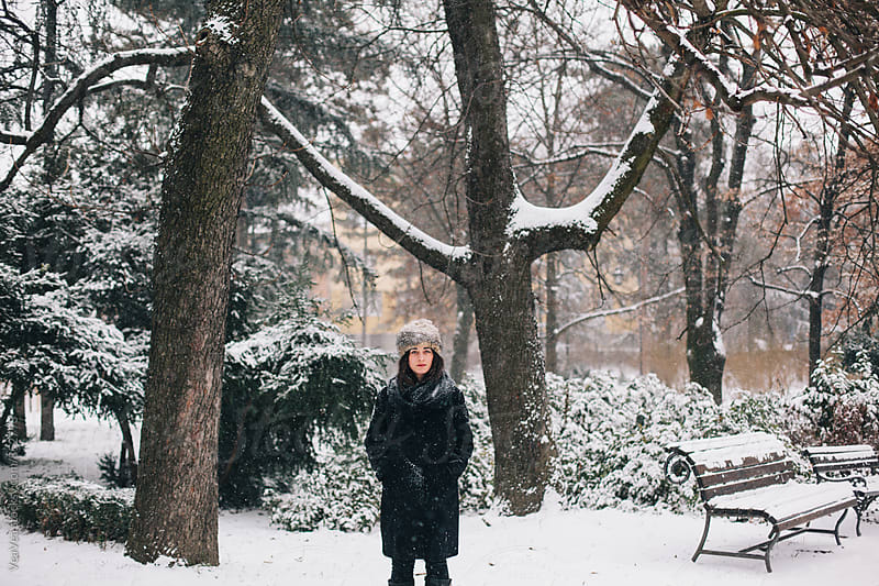 Stylish woman standing in the park during a snowy day by VeaVea for Stocksy United