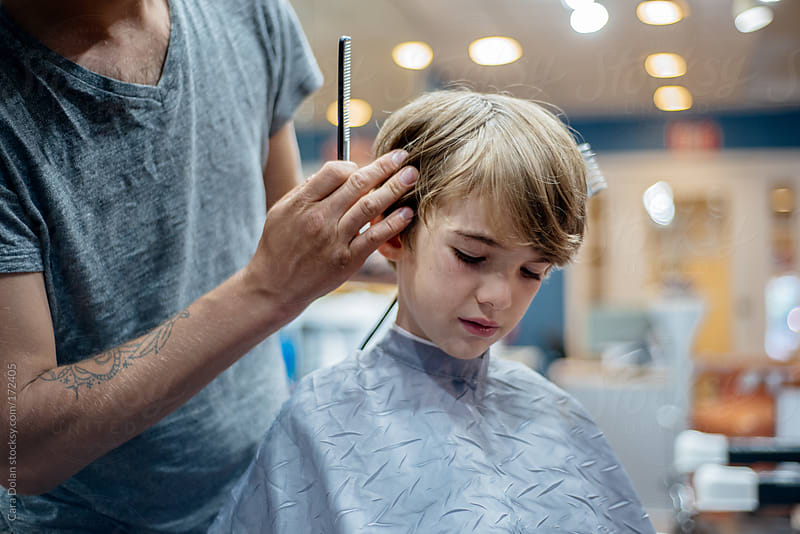 Stylist getting ready to cut a young boy's hair by Cara Dolan for Stocksy United