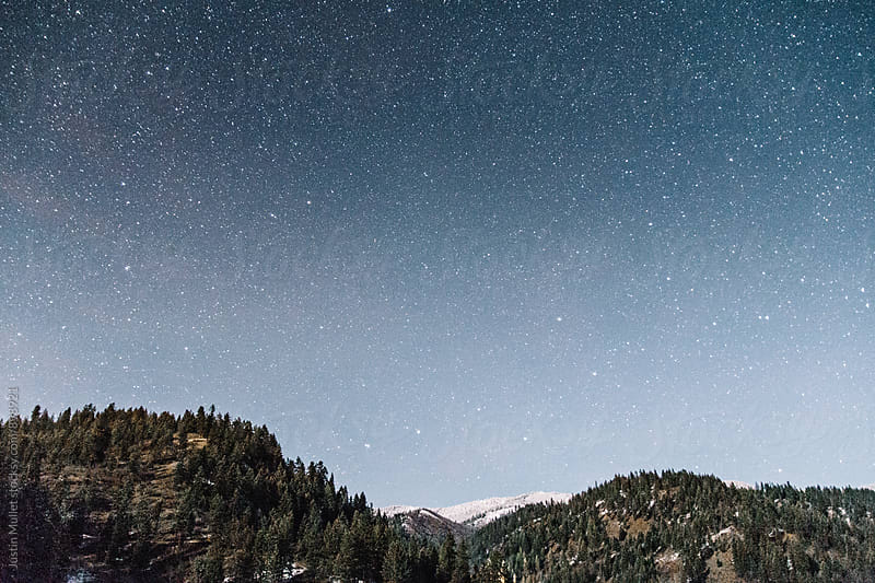 Starry sky over mountains with fresh snow.  by Justin Mullet for Stocksy United