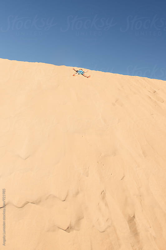Boy doing a sand angel at the top of a large sand dune against a blue sky by Angela Lumsden for Stocksy United