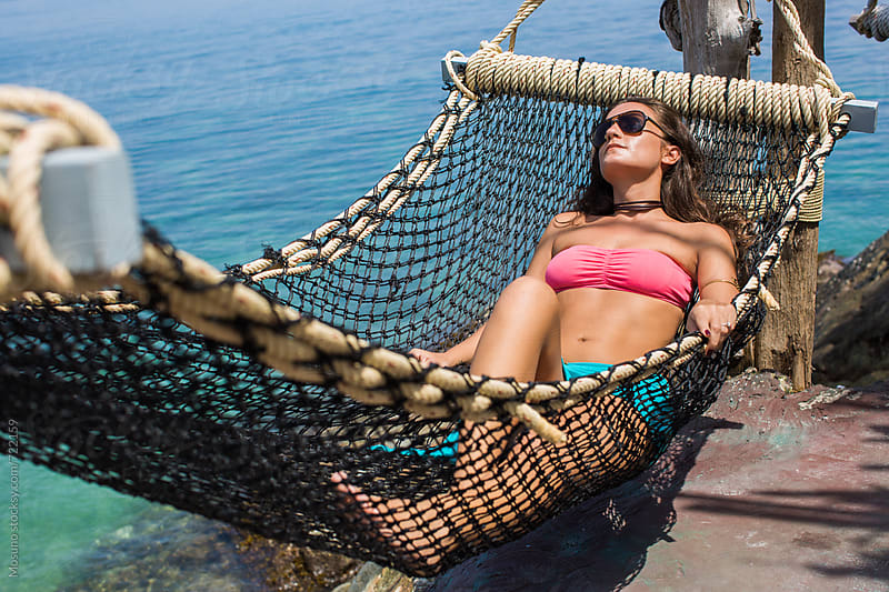 Woman Sunbathing in a Hammock by Mosuno for Stocksy United