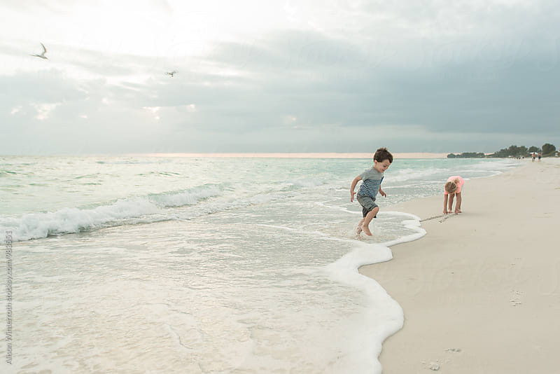 Children Playing At The Beach With A Drone In The Background by Alison Winterroth for Stocksy United