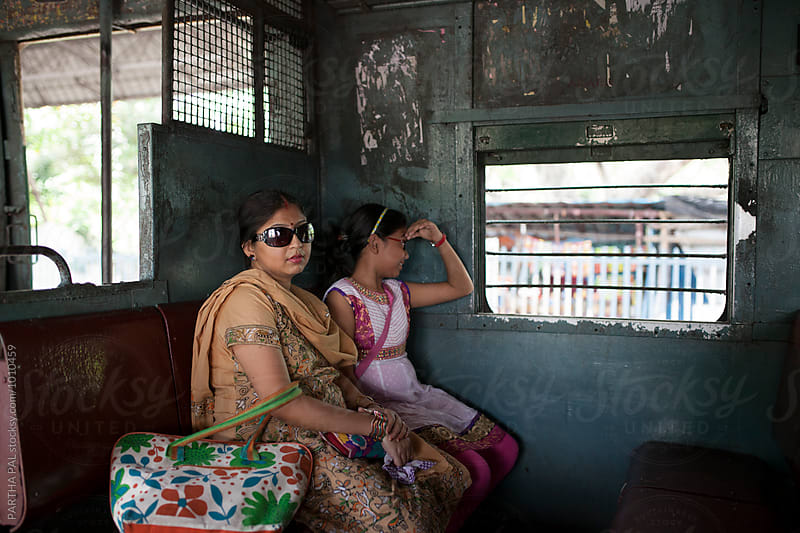 A mother and daughter traveling in Indian local Train by PARTHA PAL for Stocksy United