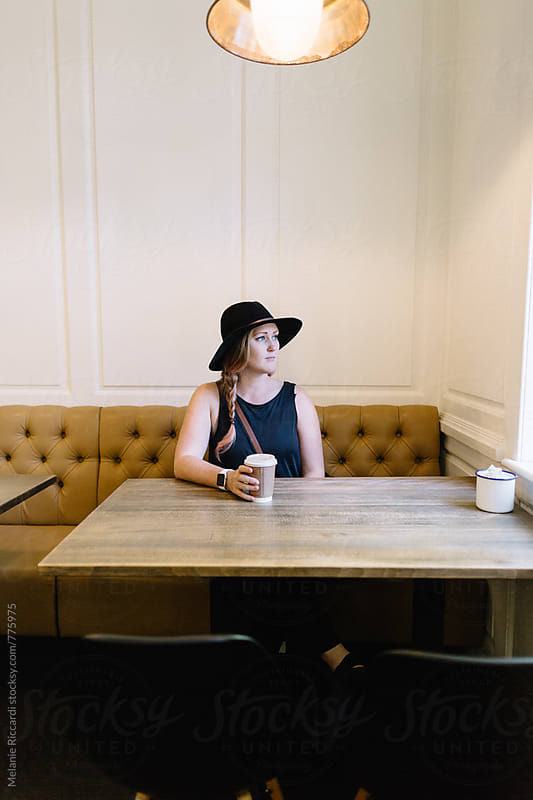 Woman sitting in a Coffee Shop by Melanie Riccardi for Stocksy United