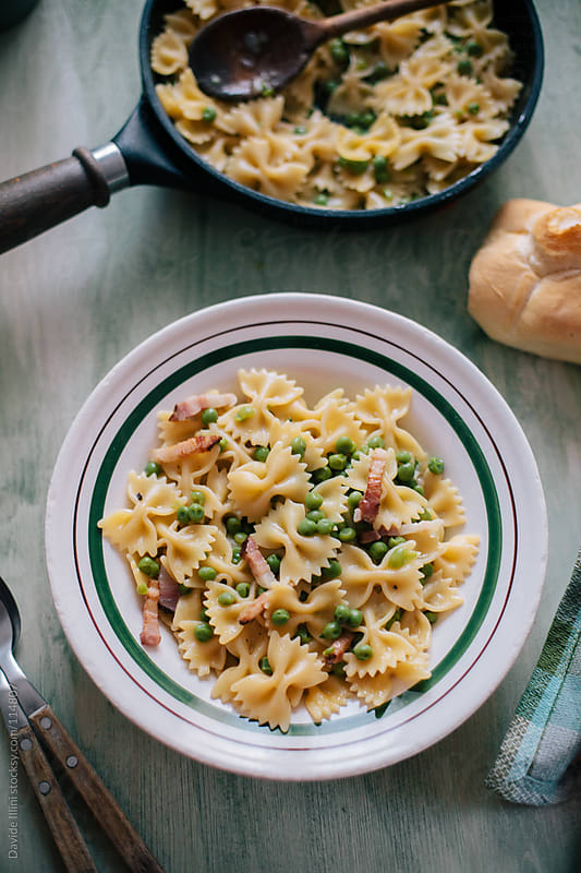 Farfalle with bacon and peas by Davide Illini for Stocksy United