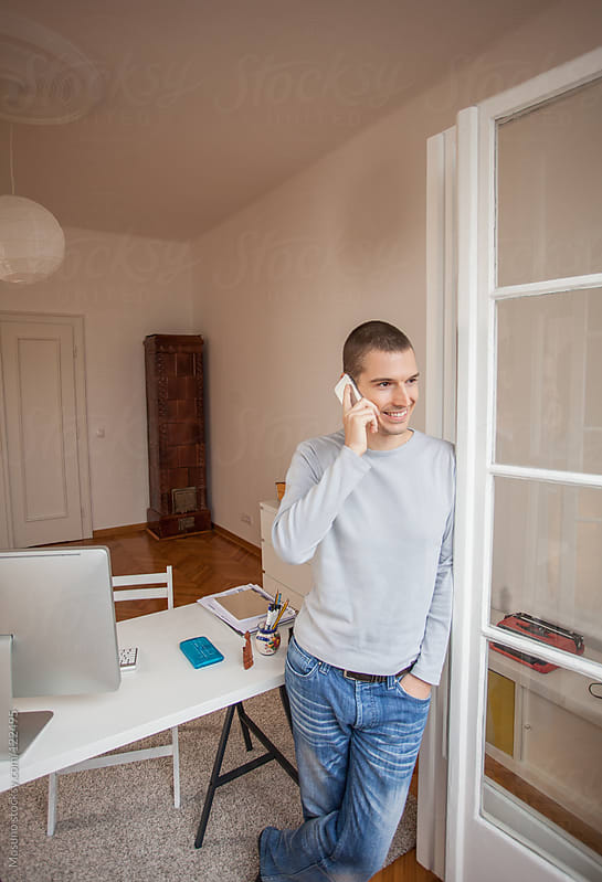Man Standing in His Home Office and Talking on the Phone by Mosuno for Stocksy United