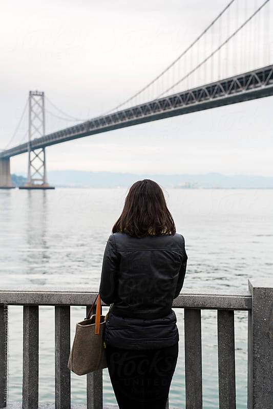 Young woman looking at Bay Bridge in San Francisco by Matthew Spaulding for Stocksy United