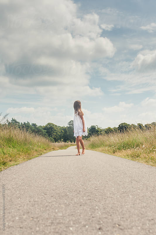 Little girl barefoot in a white dress walking on a long road by Cindy Prins for Stocksy United