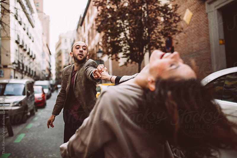 couple dancing in the street by Thais Ramos Varela for Stocksy United