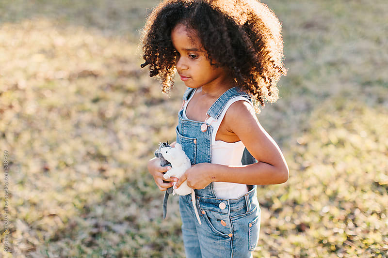 A little girl with curly hair playing in the backyard with her toys. by Kristen Curette Hines for Stocksy United