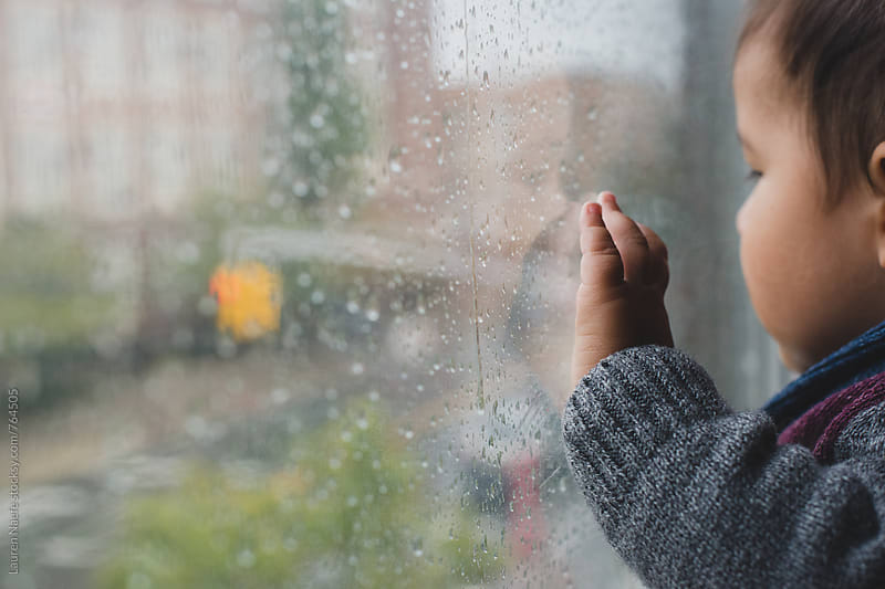 Baby looking out window on rainy day by Lauren Naefe for Stocksy United