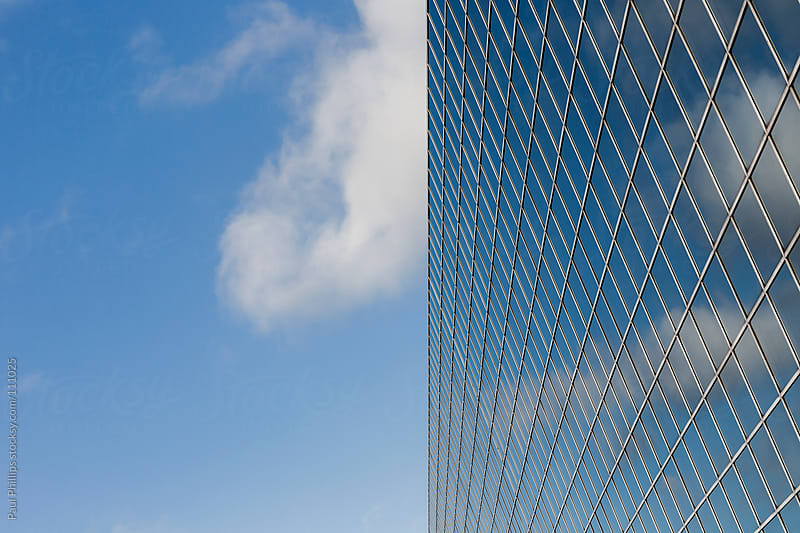 Modern office block reflecting clouds in the windows by Paul Phillips for Stocksy United