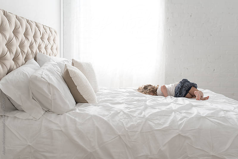 Baby Boy Lays In A Big White Bed by Alison Winterroth for Stocksy United