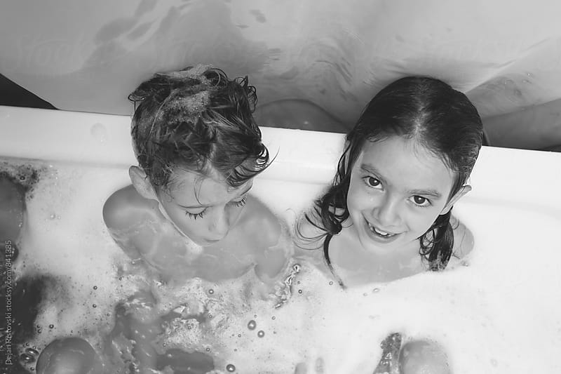 Girl and boy taking bath. by Dejan Ristovski for Stocksy United