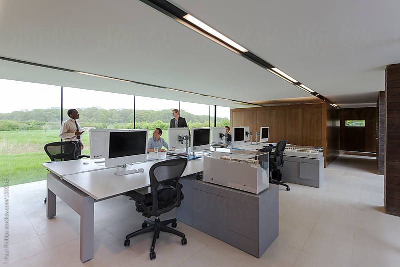 Contemporary office with large white table staff and monitors  by Paul Phillips for Stocksy United
