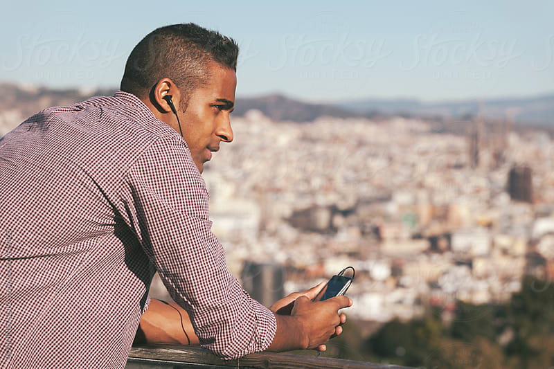 Black young man listening music with his phone and enjoying a nice panorama of Barcelona.  by BONNINSTUDIO for Stocksy United