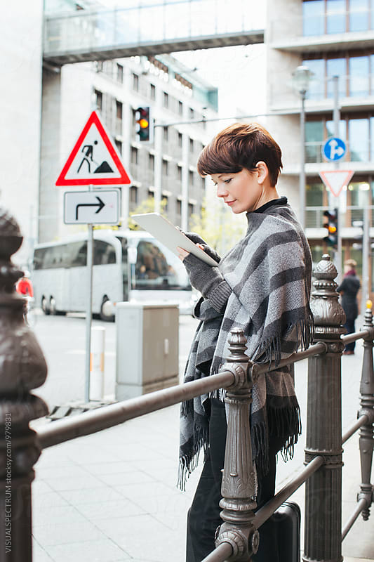 Pretty Caucasian Woman Standing in Street and Using Digital Tablet by Julien L. Balmer for Stocksy United