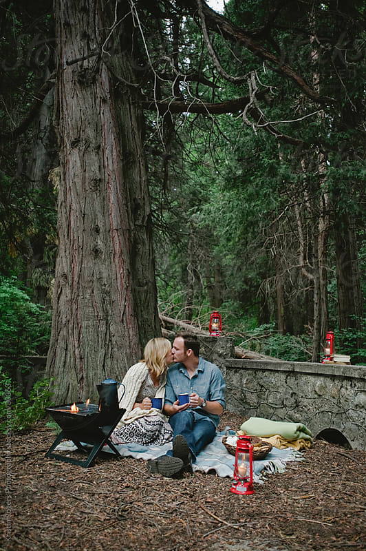 Couple on romantic camping date making hot chocolate and eating smores by Kristin Rogers Photography for Stocksy United