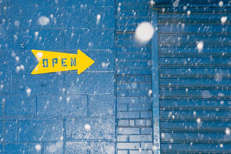 Open sign during snowstorm by Kristin Duvall for Stocksy United