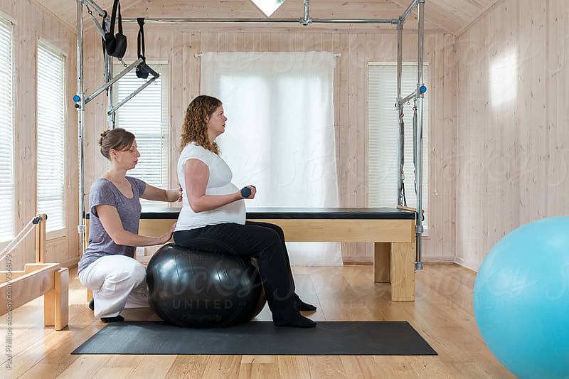 Pilates instructor guiding a pregnant woman through mental exercise whilst seated on a pilates ball by Paul Phillips for Stocksy United