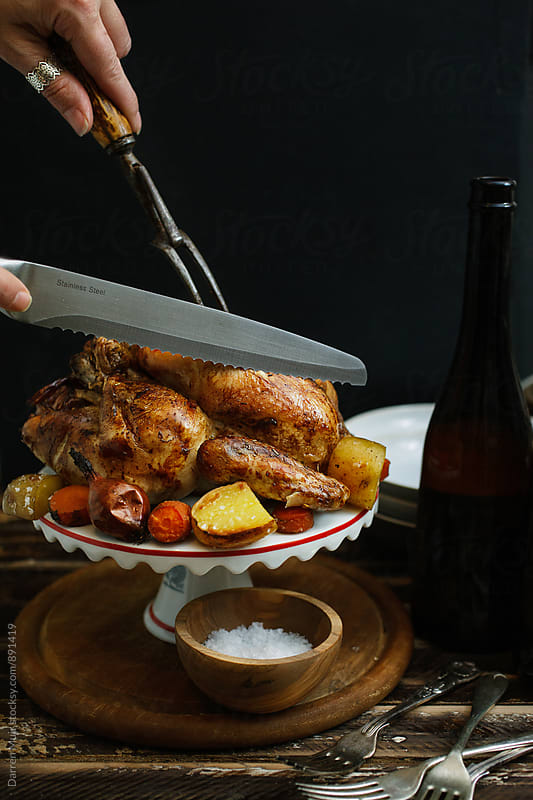 Carving a chicken. Roast chicken. by Darren Muir for Stocksy United