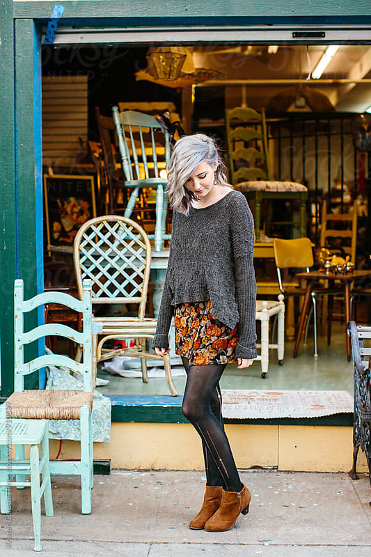 A woman standing in front of an antiques thrift store with various items displayed. by Kristen Curette Hines for Stocksy United