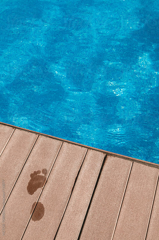 Wet Footprint on a Wooden Floor by the Pool by VICTOR TORRES for Stocksy United