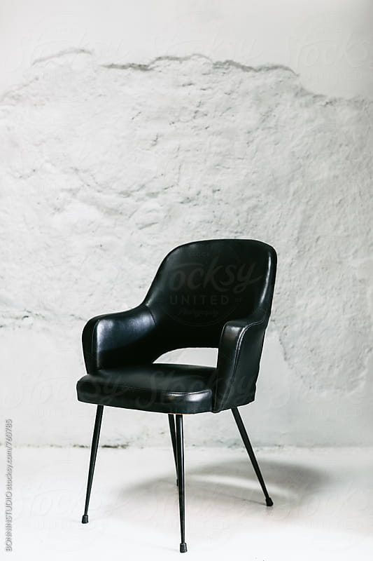 Black armchair on white wall. by BONNINSTUDIO for Stocksy United