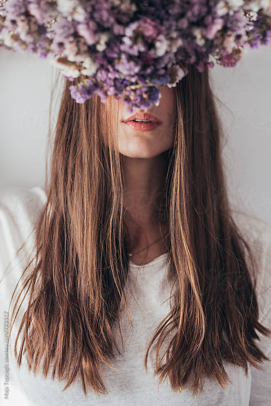 Portrait of a beautiful woman with flowers in front of her head by Maja Topcagic for Stocksy United